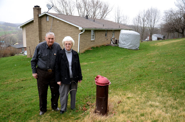 Jesse and Shirley Eakin stand by the water well they no longer use at their home in Avella, Pa. Delivered water is stored in the tank behind them.