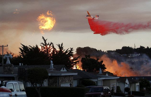 A plane spreads fire retardent on the San Bruno fire.