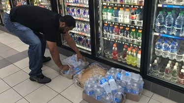 Keith Delahoussaye puts single bottles of water into a box after grabbing them from the cooler at a Beaumont convenience store early Thursday morning.    Photo/Scott Eslinger-KBMT