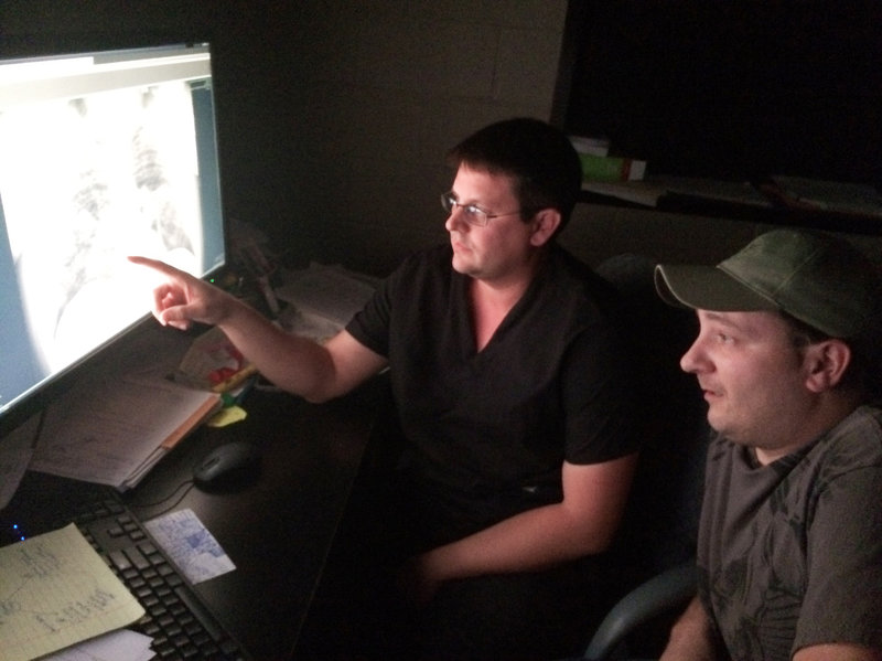 Radiologist Brandon Crum and former coal miner Mackie Branham, 39, view an X-ray of Branham's diseased lung at Crum's black lung clinic in Coal Run Village, Ky. Howard Berkes/NPR