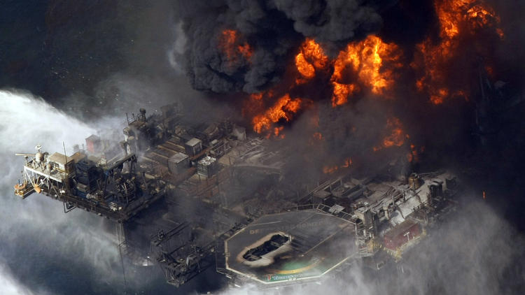 BP's Deepwater Horizon oil platform burns in April 2010, fouling the Gulf Coast: Is it responsible for a massive die-off of dolphins? (Gerald Herbert / Associated Press)