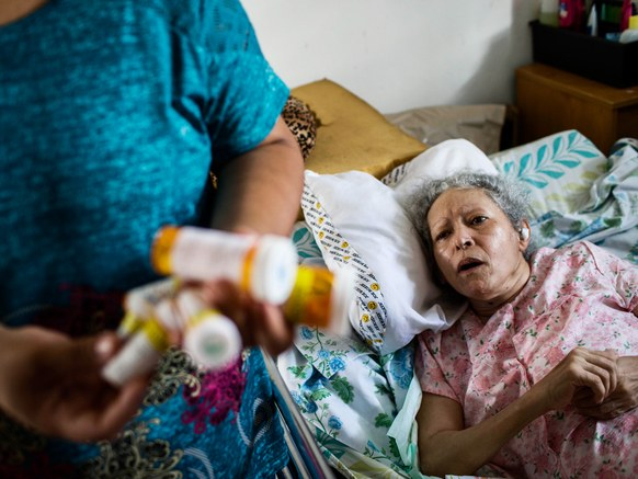 Marry Ann Aldea hands her mother medicine at her home in Juncos, Puerto Rico.DENNIS M. RIVERA PICHARDO/THE WASHINGTON POST/GETTY IMAGES